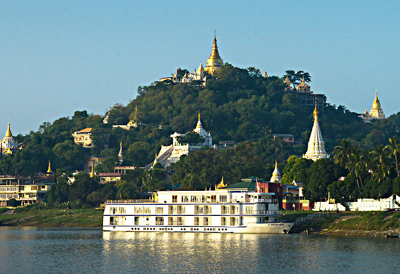 Temples and cruise boat line the Irrawaddy River bank